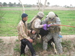 """1st Sgt. Ken Baum and a US soldier hold down and treat an ornery cow during a Veterinary Civic Action Program (VETCAP) misson near Albu Aifan. The Army vet is running hose down the animal's throat to treat """"gastro bloat."""" Photo courtesy of Alex Albrecht"""